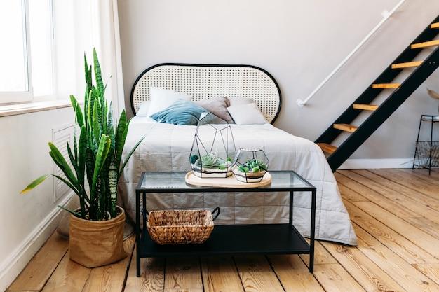Interno di una stanza con un letto e un tavolo, fiori e vasi di vetro con piante