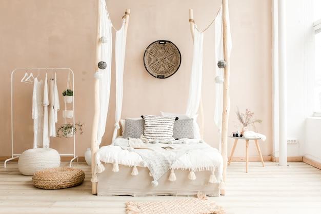 Interno della spaziosa camera da letto in stile scandinavo con letto grigio e pianta di ficus in una pentola