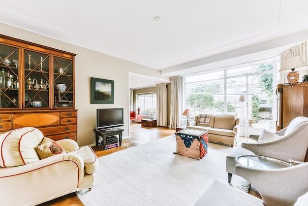 Interno di elegante soggiorno con comodo divano e poltrone con tavolo in legno