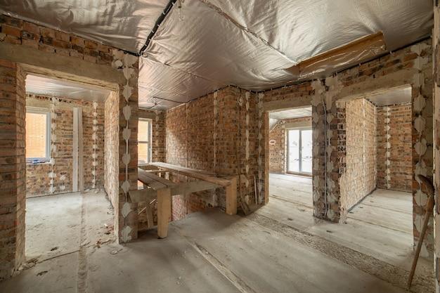 Interno della casa di mattoni non finita con pavimento in cemento e pareti nude pronte per intonacare in costruzione. sviluppo immobiliare
