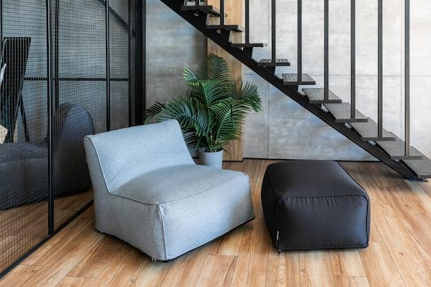 Interno del giovane appartamento di laurea in stile loft con mobili in primo piano, scala in metallo e guardaroba in background