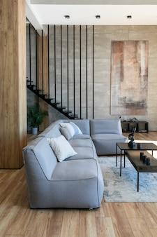 Interno del giovane appartamento di laurea in stile loft con mobili morbidi in primo piano,