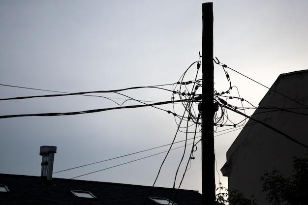 Fili elettrici intrecciati in una grande città contro il cielo. silhouette di un pilastro