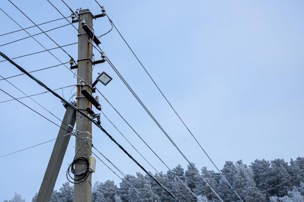 Intreccio di fili elettrici con luci contro il cielo e la foresta. sagoma di un pilastro