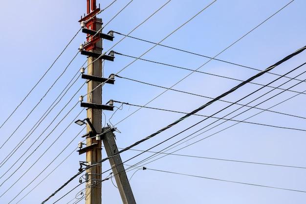 Intreccio di fili elettrici con luci contro il cielo. sagoma di un pilastro