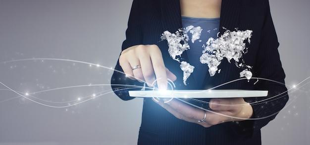 Concetto di affari internazionali. compressa bianca in mano della donna di affari con il segno della mappa di workd dell'ologramma digitale su fondo grigio. concetto di tecnologia mondiale dei media.