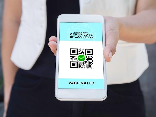 Certificato internazionale di vaccinazione, passaporto digitale intelligente con codice qr sullo schermo dello smartphone. chiuda sulla mano della donna vaccinata che mostra il passaporto sanitario della certificazione di vaccinazione.