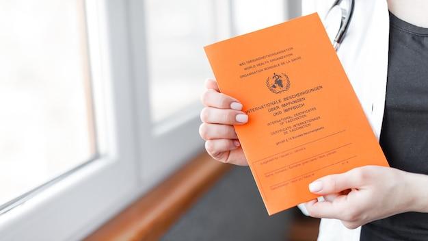 Certificato internazionale di vaccinazione con testo tedesco e inglese sulla mano della donna. concetto di vaccino