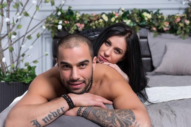 Coppia internazionale di uomo con petto nudo e con le mani tatuate, donna bruna sdraiata su di lui sul letto grigio accogliente in camera da letto
