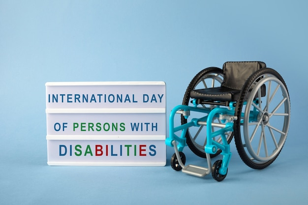 Giornata internazionale delle persone con disabilità. sedia a rotelle su sfondo blu Foto Premium