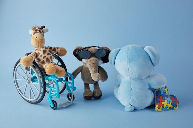 Giornata internazionale delle persone con disabilità. sedia a rotelle con segno di giocattoli di diverse disabilità su sfondo blu.