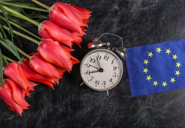 Festa internazionale, europea. giorno della conoscenza, giorno dell'insegnante. bouquet di tulipani, sveglia, bandiera dell'unione europea su uno sfondo di lavagna.
