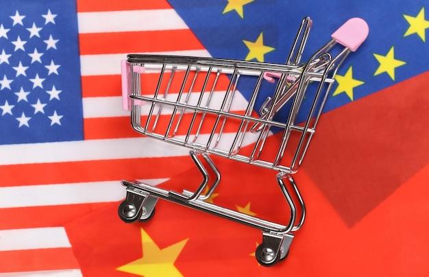 Supermercato internazionale e globale. mini carrello della spesa sullo sfondo della bandiera sfocata degli stati uniti, della cina e dell'unione europea. concetto di acquisto.
