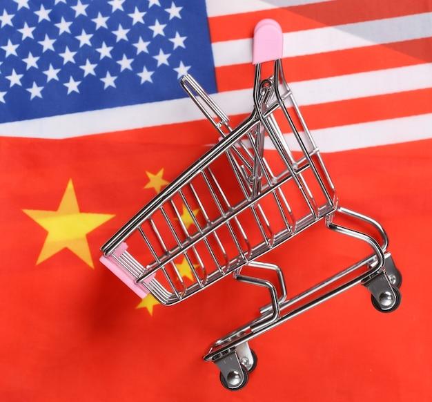 Supermercato internazionale e globale. mini carrello della spesa sullo sfondo della bandiera sfocata degli stati uniti e della cina. concetto di acquisto.