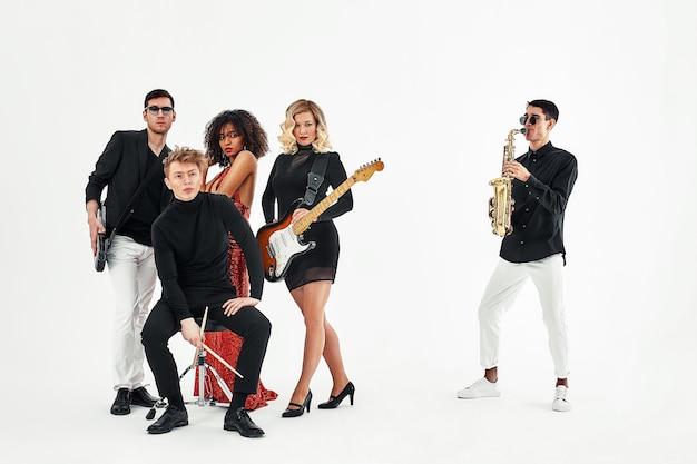 Gruppo internazionale di musicisti su sfondo bianco, chitarrista, batterista, solisti, sassofonista. copia spazio, relkama per strumenti musicali.