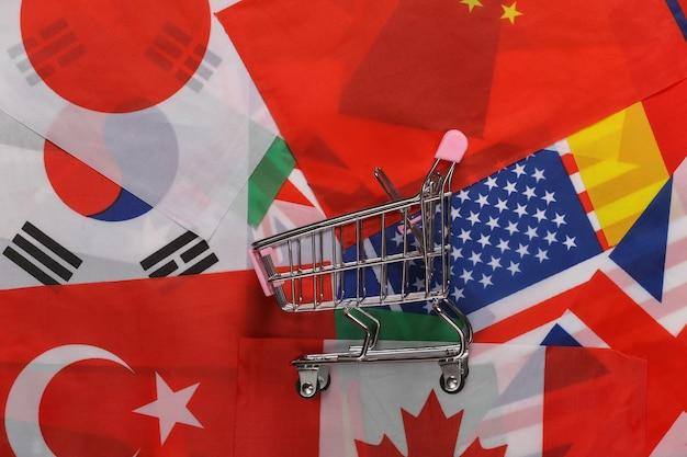 Acquisti internazionali. carrello della spesa sullo sfondo di molte bandiere dei paesi