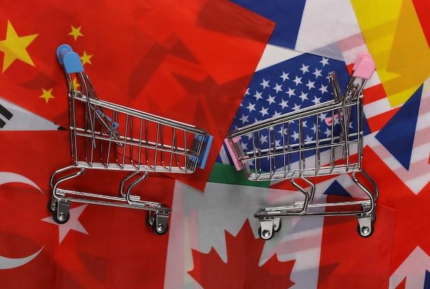 Acquisti internazionali. carrelli della spesa sullo sfondo di molte bandiere dei paesi