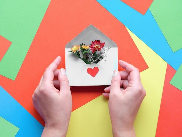 Giornata internazionale grazie. biglietto di auguri con le mani che tengono la busta con fiori su carta a strati