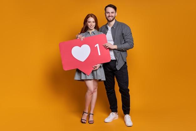 Blog su internet. ritratto di coppia carina in abbigliamento da festa tenendo il cuore come icona, consigliando di fare clic