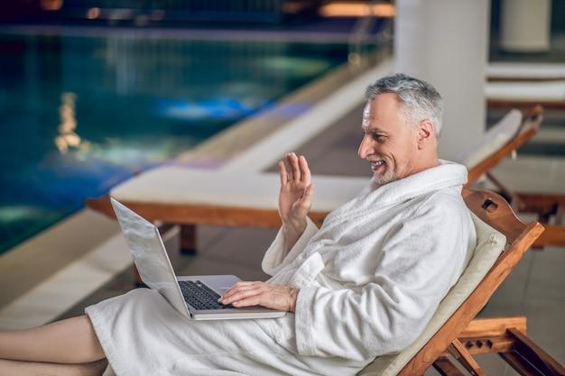 Su internet. un uomo barbuto dai capelli grigi con indosso un accappatoio bianco che passa del tempo su internet