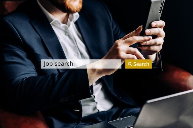 Concetto di barra di ricerca di lavoro su internet sullo sfondo di un uomo d'affari con lo smartphone.