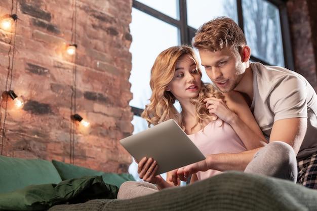 Su internet. coppia appena sposata che cerca il posto per la cena in internet utilizzando il tablet mentre è seduto in camera da letto