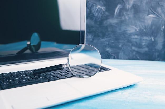 Concetto di ricerca su internet, lente d'ingrandimento e tastiera del computer