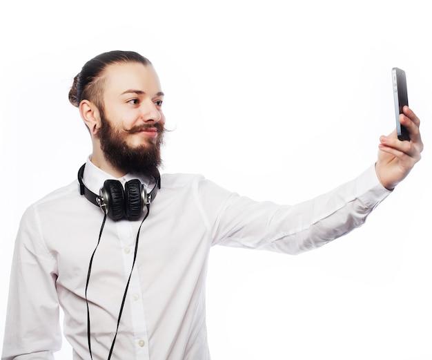 Internet, tecnologia e concetto di persone: un giovane con la barba in camicia che tiene il telefono cellulare e fa una foto di se stesso mentre si trova in piedi su sfondo bianco.
