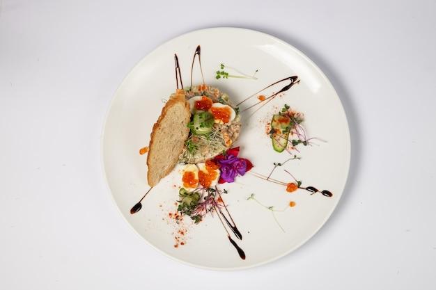 Interpretazione dell'insalata di olivier con filetto di pollo alla griglia, uova di quaglia e caviale rosso, su una superficie bianca. vista dall'alto