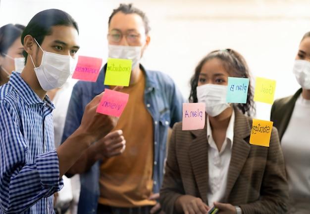 Idea di brainstorming del team aziendale asiatico interrazziale nella sala riunioni dell'ufficio dopo la riapertura a causa del blocco della città del coronavirus covid-19. indossano una maschera facciale per ridurre il rischio di infezioni come nuovo normale stile di vita.