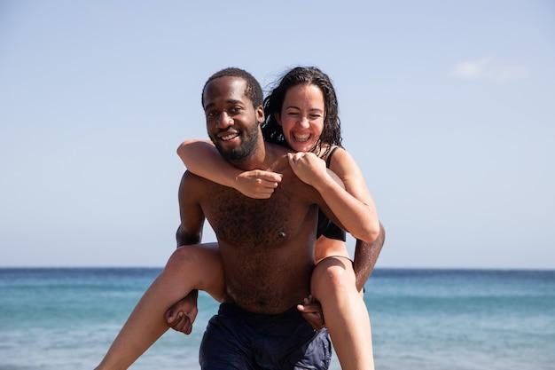 Coppia interrazziale sulla spiaggia, uomo africano solleva una donna caucasica, in estate si godono le vacanze e si divertono