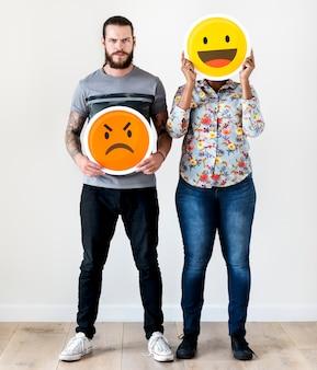 Le coppie interrazziali che tengono un'emoticon espressivo affrontano l'espressione facciale aggrottare le sopracciglia e sorridere relationshi