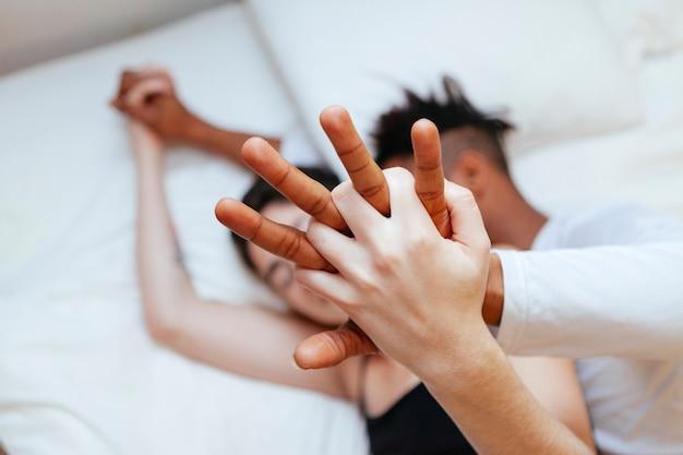 Coppie interrazziali che si tengono per mano a casa. giovane amore millenario tra due razze diverse.