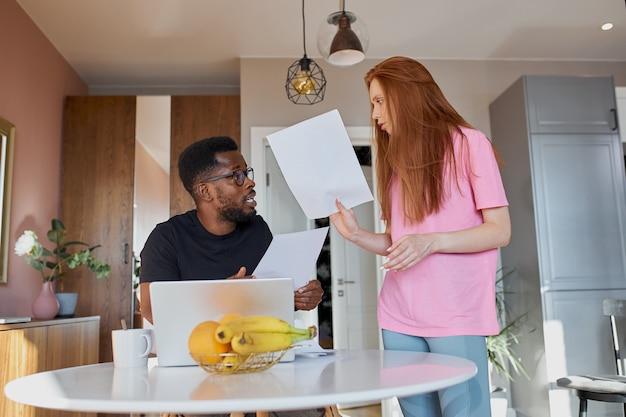 Coppie interrazziali che leggono la posta e controllano la contabilità in cucina a casa