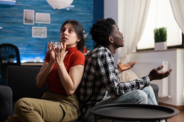 Coppia interrazziale che urla mentre è seduto sul divano. persone di razza mista arrabbiate che litigano per problemi matrimoniali mentre urlano. partner multietnici che litigano sentendosi irritati
