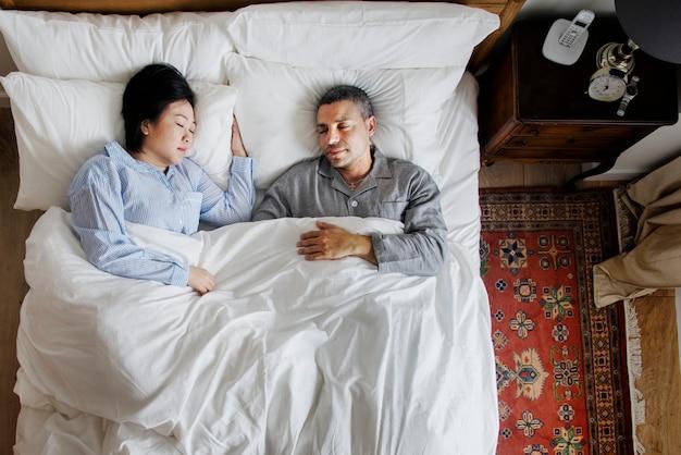 Coppie interrazziali che dormono insieme sul letto