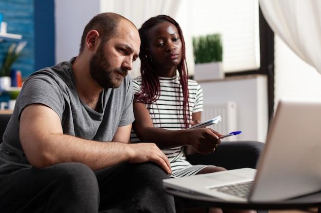 Coppia interrazziale che utilizza laptop per il pagamento delle tasse e l'economia a casa. persone di razza mista che tengono conto del budget finanziario e del denaro delle tasse durante l'utilizzo del dispositivo con la tecnologia.