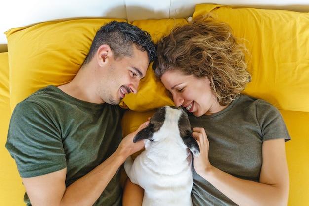 Momento intimo di coppia con animale domestico a casa sul letto. vista dall'alto orizzontale che gioca con l'animale domestico all'interno.