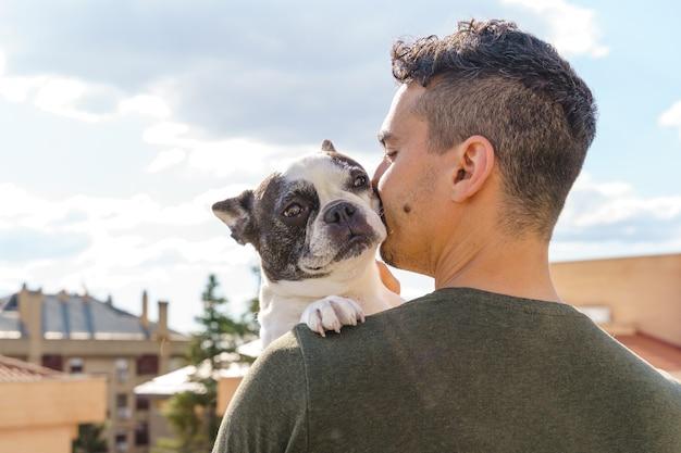 Momento intimo dell'uomo irriconoscibile che bacia il cane all'aperto. vista laterale orizzontale dell'uomo che ama il suo cane.