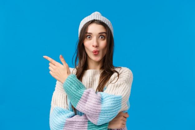 Donna sorridente carina incuriosita ed eccitata in maglione invernale