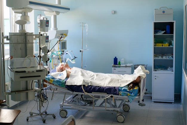 Uomo bianco adulto intubato sotto avl che giace in coma nel reparto di terapia intensiva. paziente in stato critico.