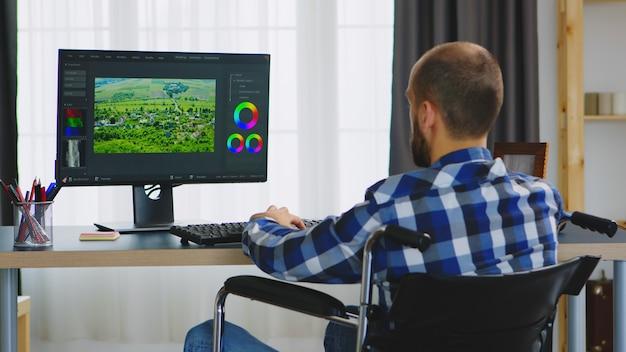 Creatore di contenuti non valido su sedia a rotelle che lavora alla post produzione video.