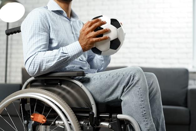 Uomo invalido o disabile seduto su sedia a rotelle e con in mano un pallone da calcio