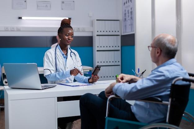 Uomo anziano invalido che riceve cure da un dottore nero