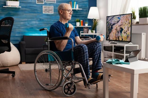Pensionato invalido in sedia a rotelle che allena la persistenza dei muscoli del corpo utilizzando il recupero dei manubri da palestra dopo la paralisi