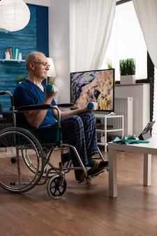 Pensionato invalido in sedia a rotelle che allena la persistenza dei muscoli del corpo utilizzando manubri da palestra