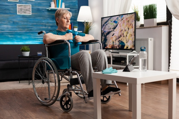 Donna anziana non valida in sedia a rotelle che allena i muscoli del corpo utilizzando il recupero di manubri ginnici dopo la paralisi