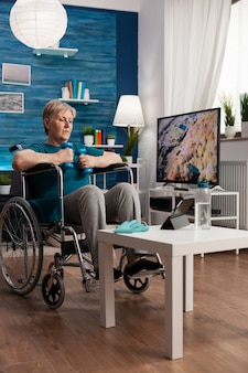 Donna anziana non valida in sedia a rotelle che allena i muscoli del corpo usando manubri ginnici