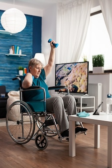 Donna anziana non valida in sedia a rotelle che guarda l'esercizio del corpo in palestra su tablet in soggiorno che esercita muscoli delle braccia usando manubri da allenamento workout