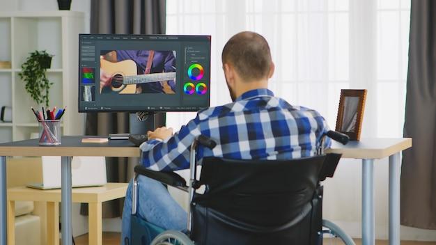 Videografo non valido in sedia a rotelle che lavora alla post produzione di film dall'ufficio di casa.